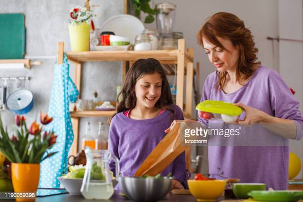 mother packing school lunch for her daughter - lunch bag stock pictures, royalty-free photos & images