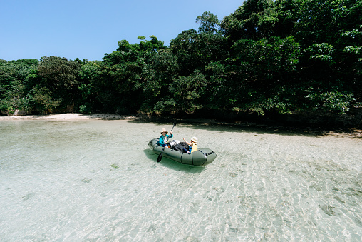 Mother paddling raft with child on clear tropical water, Ishigaki Island, Japan - gettyimageskorea