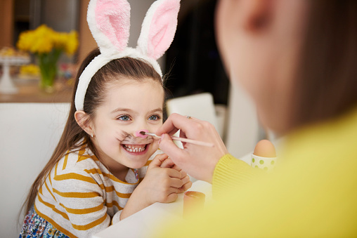 Mother painting daughter's face wearing bunny ears - gettyimageskorea