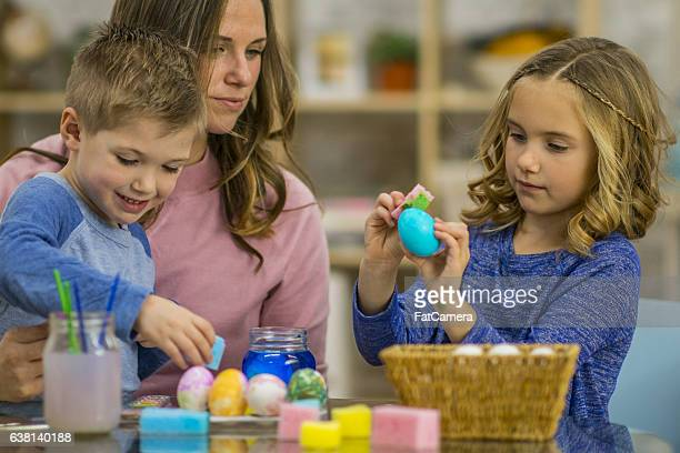 Mother Painting Eggs with Her Children
