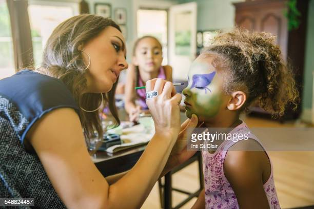 mother painting face of daughter in living room - body paint stock pictures, royalty-free photos & images