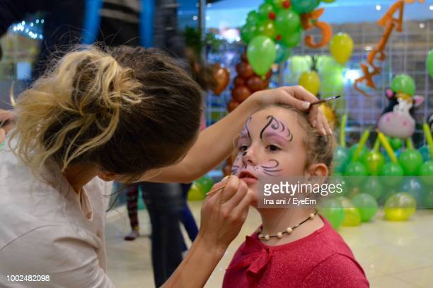 mother painting face of daughter - face paint stock pictures, royalty-free photos & images