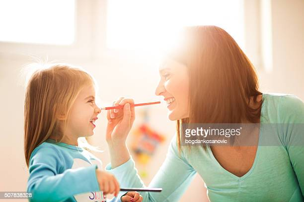 Mother painting face to her daughter