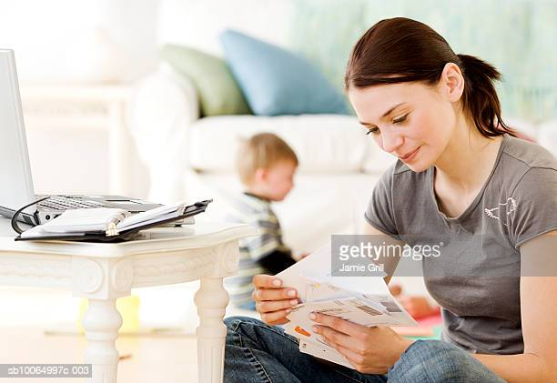 Mother paying bills online, son (21-24 months) playing in background