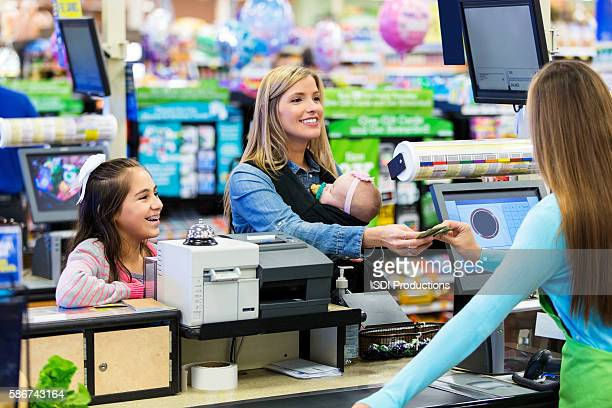 Mother paying for groceries at checkout counter with children