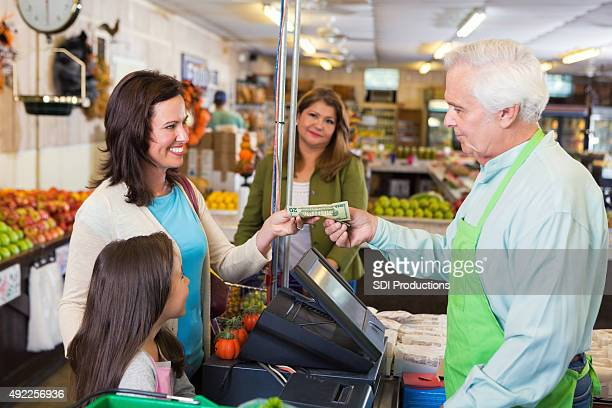 Mother paying for groceries in local market