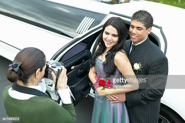 mother photographing couple departing for their high school prom - prom stock pictures, royalty-free photos & images