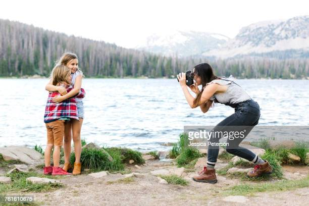 mother photographing girl (8-9) and boy (6-7) by lake - mirror lake stock pictures, royalty-free photos & images