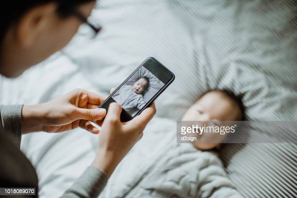 mother photographing her baby girl with mobile phone on bed joyfully - bedroom photos - fotografias e filmes do acervo