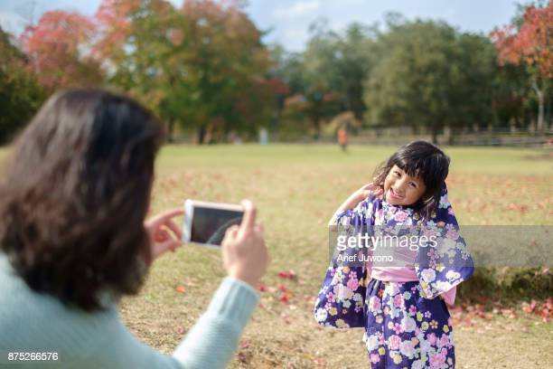 mother photographing her daughter - childhood photos ストックフォトと画像