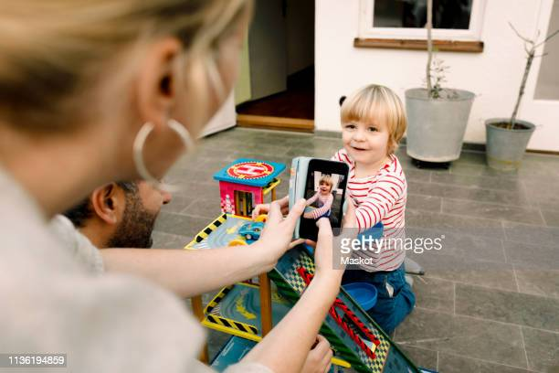 mother photographing smiling daughter playing with toy cars on porch - 写真を撮る ストックフォトと画像