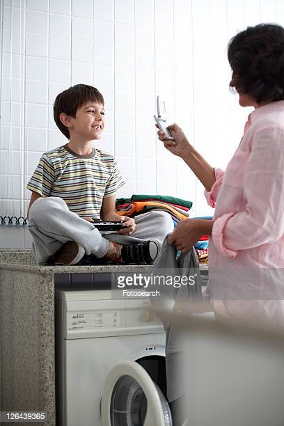 Mother photographing son in laundry room