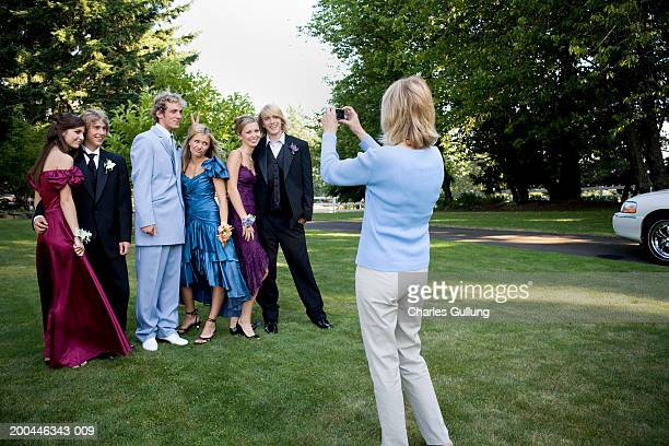 Mother photographing three teenage couples (15-18) in formalwear