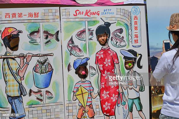 A mother photographs her children as they pose inside a cutout display The twoday 25th Annual Hong Kong Dragon Boat Festival was held in Flushing...