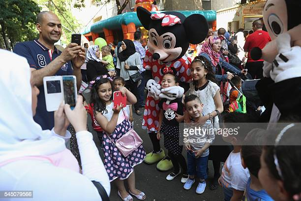 A mother photographs her children with actors wearing Mickey and Minnie Mouse costumes during a street fest in immigrantheavy Neukoelln district to...