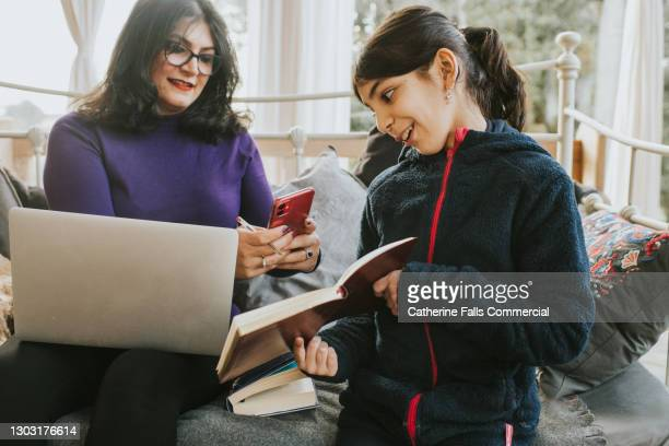 mother photographs her daughters homework with a mobile phone - inconvenience stock pictures, royalty-free photos & images