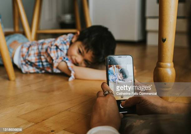 a mother photographs her young son on a mobile phone - alternative pose stock pictures, royalty-free photos & images