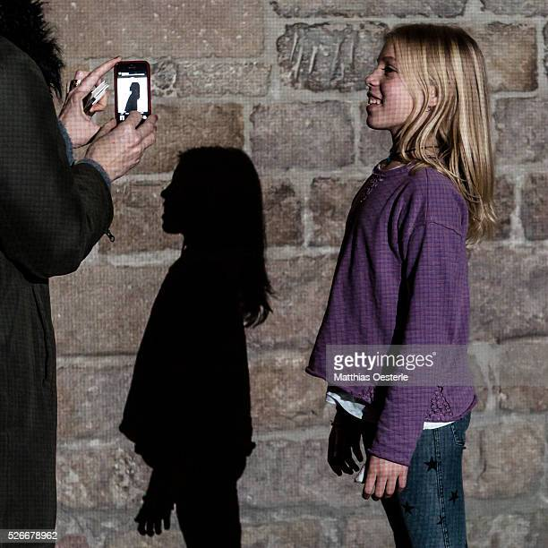 A mother photographs the shadow of her daughter as she casts her shadow at the 'Placa del Rei' during the city's light festival 'Llum BCN' in...