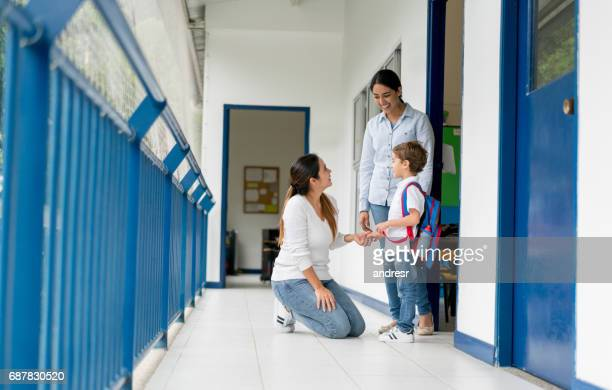 mother picking up her kid from school and talking to the teacher - genitori foto e immagini stock