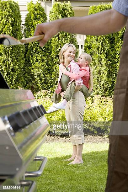 Mother piggyback with daughter at home during backyard cookout