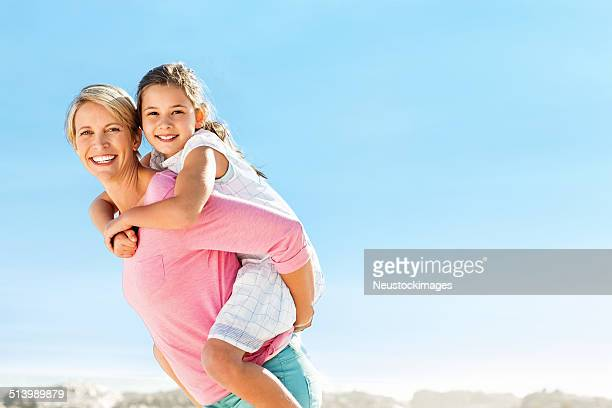 Mother Piggybacking Daughter Against Clear Blue Sky On Beach