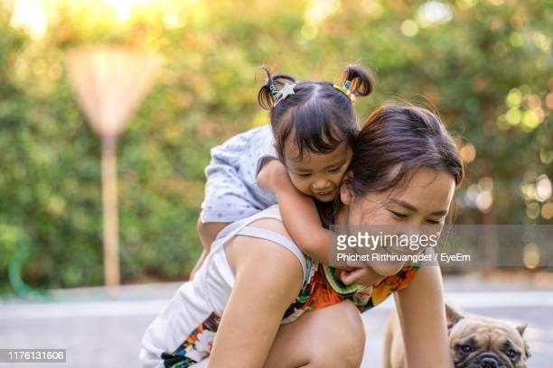 mother piggybacking daughter against trees - phichet ritthiruangdet stock photos and pictures