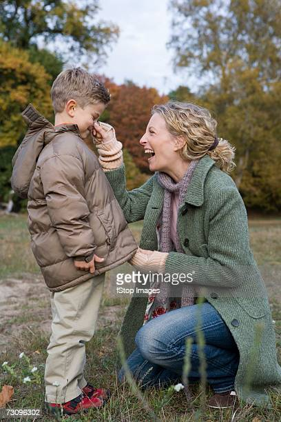Mother pinching son?s nose in park whilst zipper up parka