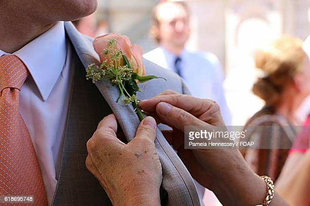 Mother pinning boutonniere on groom's suit