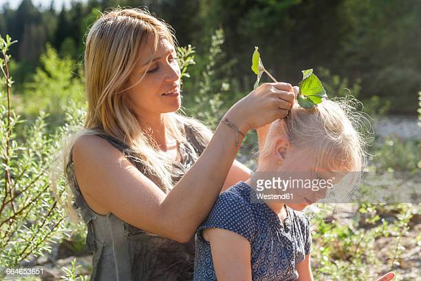 Mother pinning leaves in her daugthers hair
