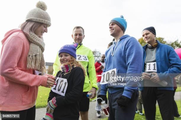 mother pinning marathon bib on daughter at charity run - 40s pin up girls stockfoto's en -beelden