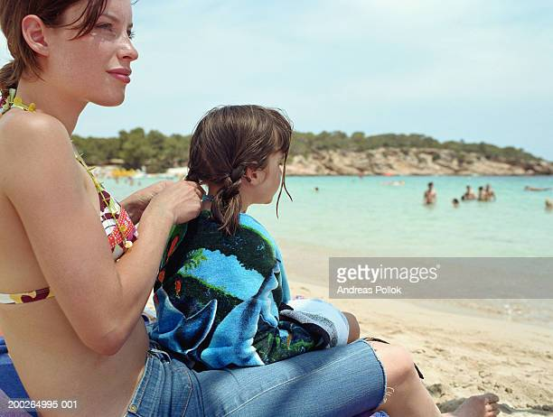 Mother plaiting daughter's (4-6) hair on beach, smiling
