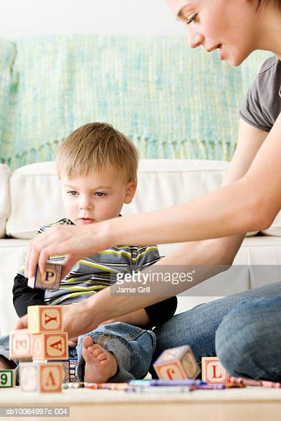 Mother playing alphabet blocks with son (21-24 months) in living room