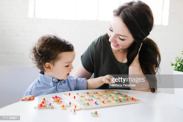 Mother playing alphabet game with son (4-5)