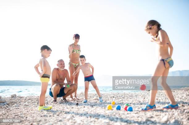 ビーチで子供たちとボッチャのプレーの母