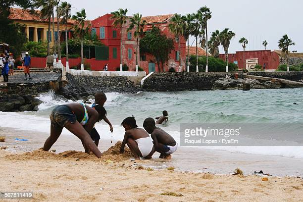 mother playing in sand with children on beach in goree island - dakar senegal stock pictures, royalty-free photos & images