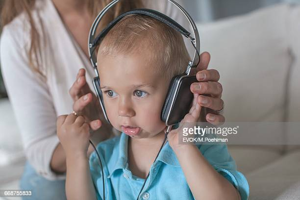 Mother playing music with headphones to son (18-23 months)