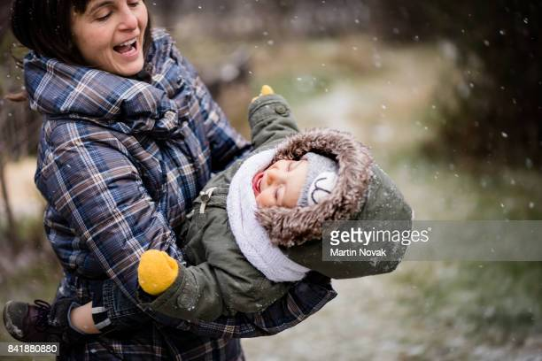 Mother playing outdoors with child during snowfall