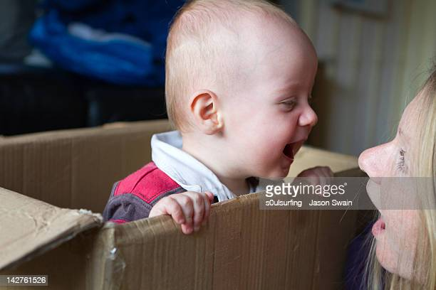 mother playing peek-a-boo with her son - s0ulsurfing stock pictures, royalty-free photos & images