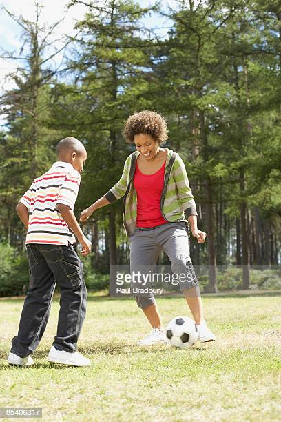 Mother playing soccer in park with son
