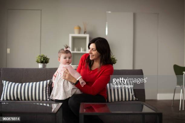 Mother playing with baby daughter on sofa at home