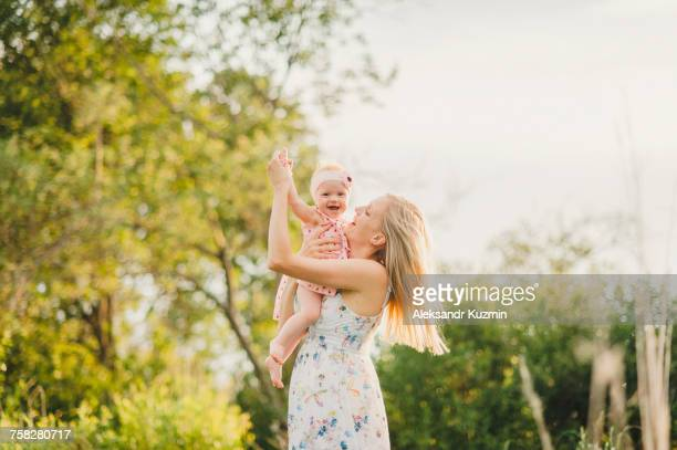 Mother playing with baby daughter on sunny day