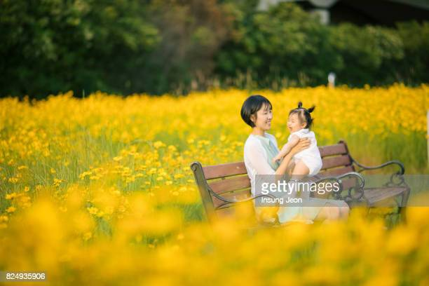 Mother playing with baby girl in yellow flower field