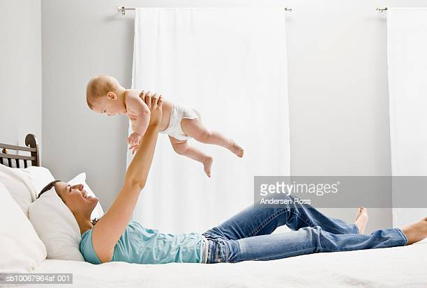 Mother playing with baby girl (8 months) on bed, side view