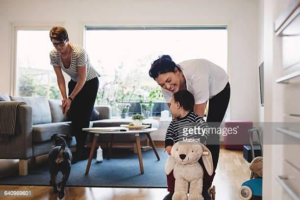 Mother playing with baby girl while woman and dog standing in living room