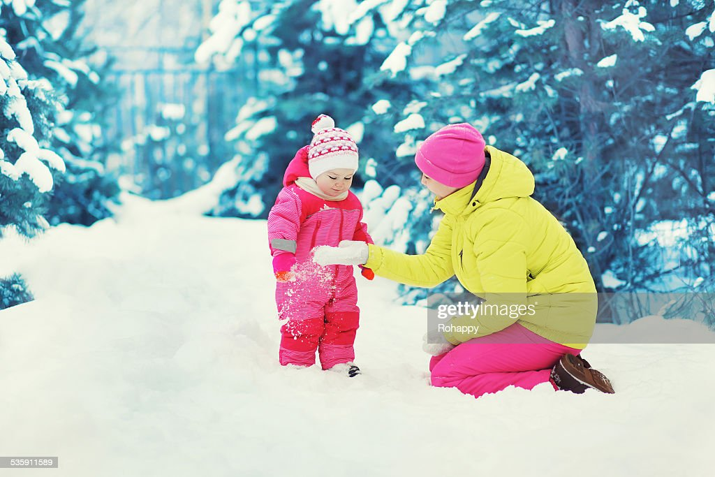Mother playing with baby in the winter snowy day : Stock Photo
