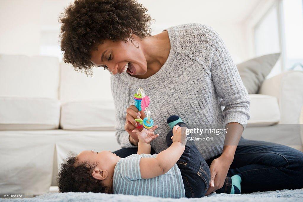 Mother playing with baby son on floor : Stock Photo