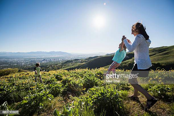 mother playing with children in filed, hiking the bonneville shoreline trail in the wasatch foothills above salt lake city, utah - salt lake city utah stock pictures, royalty-free photos & images