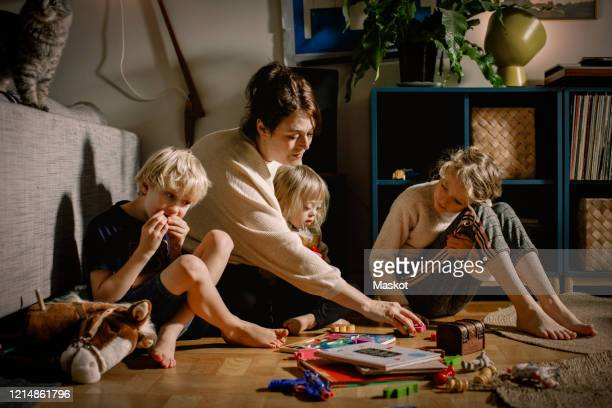 mother playing with children while sitting on floor at home - leisure games stock pictures, royalty-free photos & images
