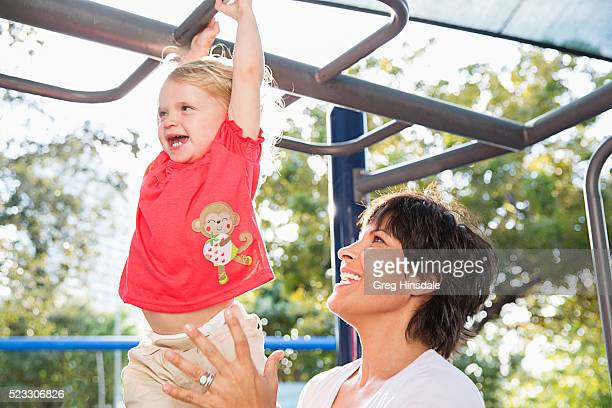 Mother playing with daughter (2-3) in playground