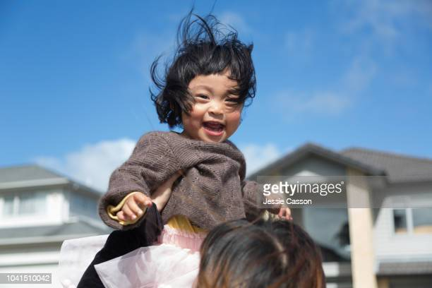 mother playing with daughter lifting her up high - candid stock pictures, royalty-free photos & images